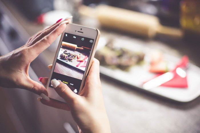 Женщина фотографирует блюдо на столе