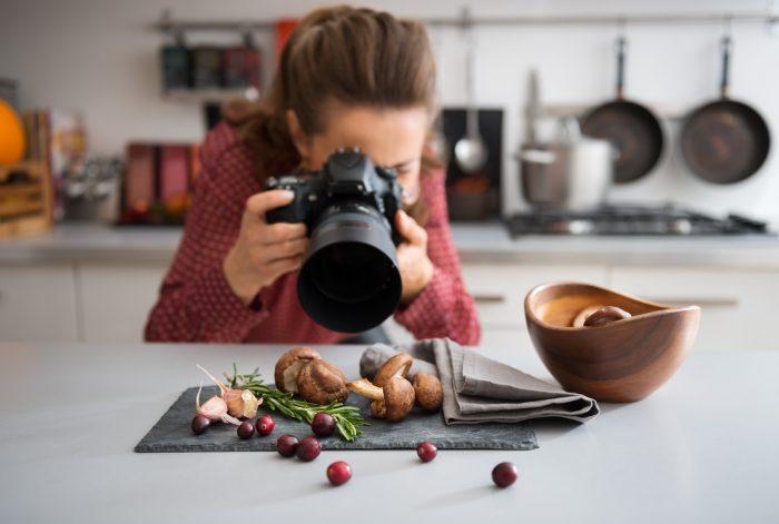 Девушка снимает натюрморт, выложенный на столе