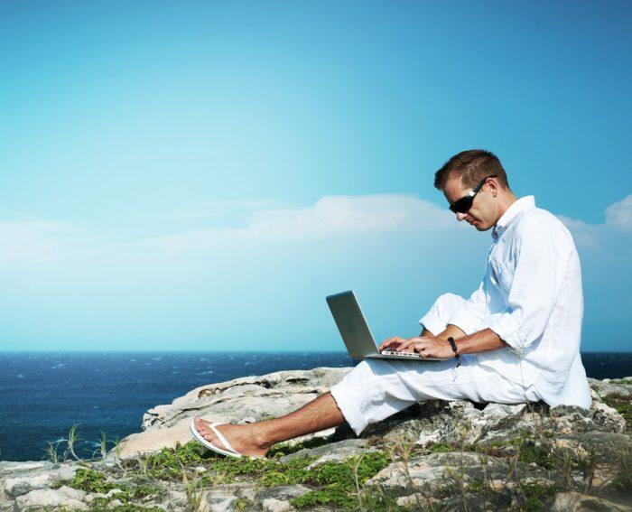 Мужчина с ноутбуком сидит на берегу моря