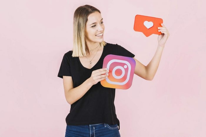 Девушка держит в руках таблички с логотипом Инстаграма и лайком