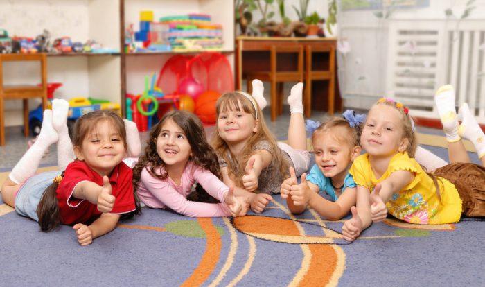 Счастливые пять девочек лежат на ковре и показывают большим пальцем руки «Класс»
