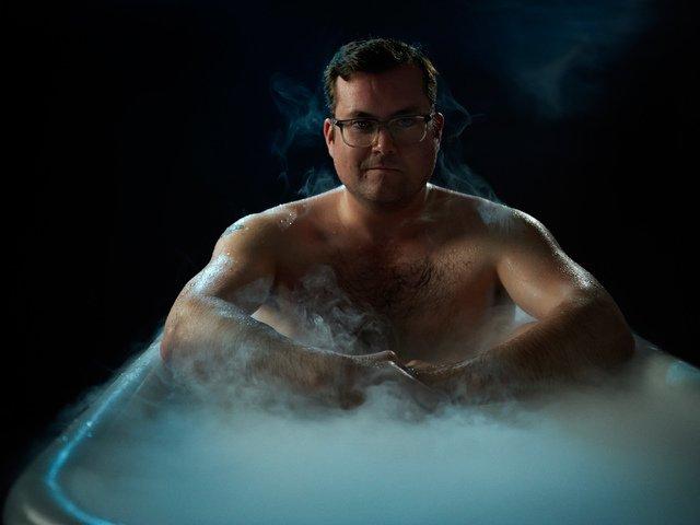 Мужчина сидит в ванне, от воды поднимается пар