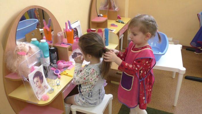 Одна девочка сидит перед зеркалом, а вторая делает ей причёску