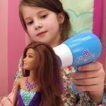 Девочка сушит феном волосы кукле Барби