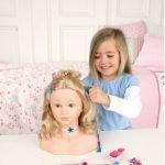 Девочка тренирует навыки парикмахера на манекене