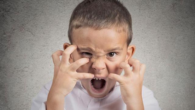 Мальчик злится, поднёс руки к лицу, словно хочет его расцарапать