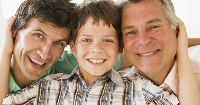 Мальчик обнимает отца и дедушку, все счастливо улыбаются