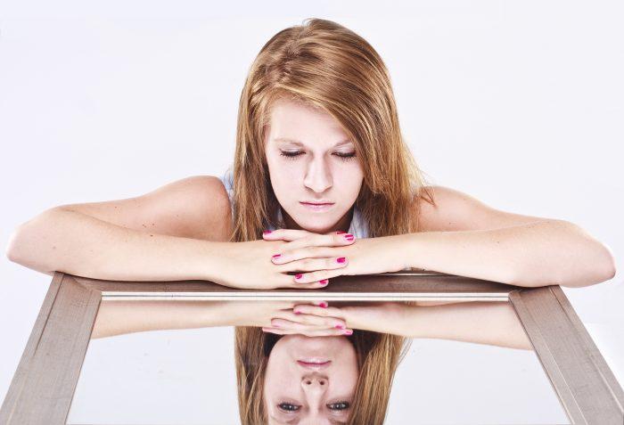 Девочка-подросток с грустью смотрит в зеркало