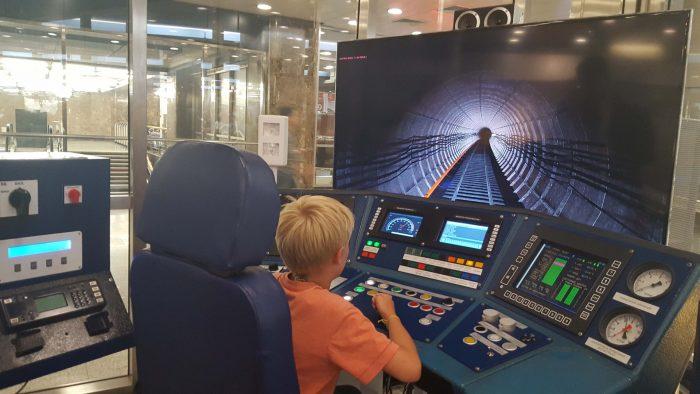 Мальчик сидит за тренажёром для машинистов метро