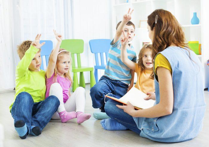 Воспитатель разговаривает с сидящим детьми