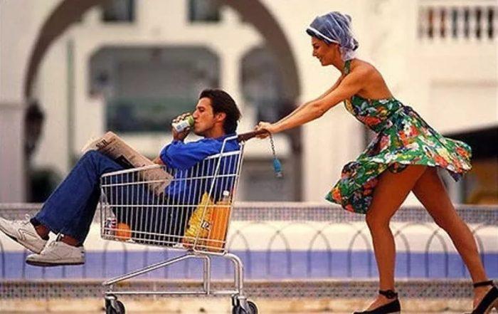 Женщина везёт в мужчину в продуктовой коляске