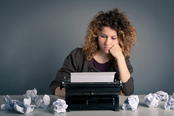 Грустная девушка за печатной машинкой и скомканные листки бумаги