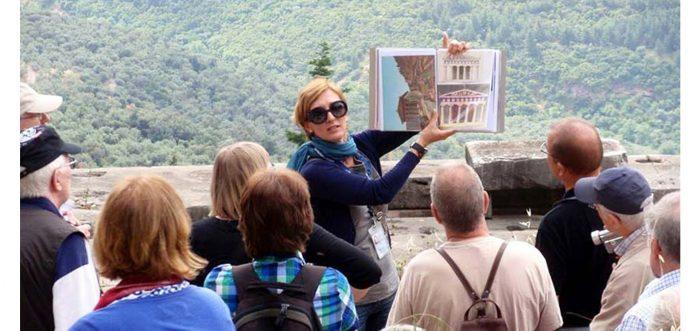 Экскурсовод показывает туристам развёрнутую книгу