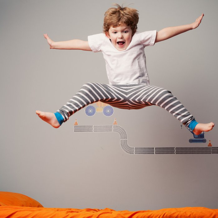 Мальчик скачет по кровати
