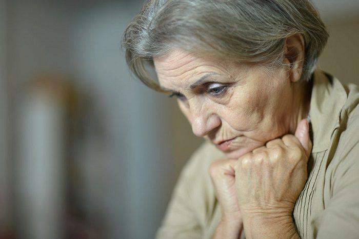 Пожилая женщина задумалась с грустным видом