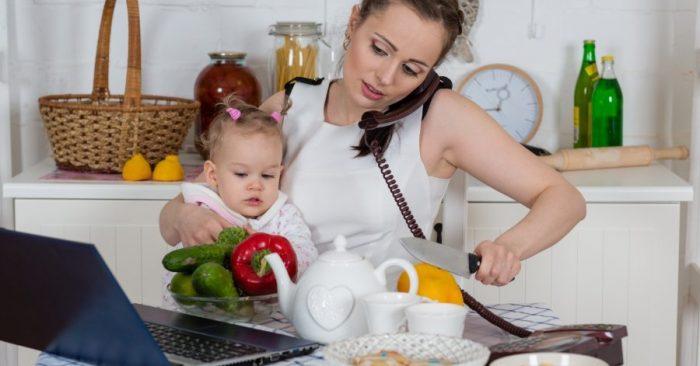 Мама держит на руках ребёнка, одновременно разговаривает по телефону, смотрит в ноутбук и режет лимон