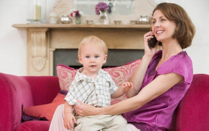 Женщина разговаривате по телефону и улыбается, на коленях сидит маленький мальчик