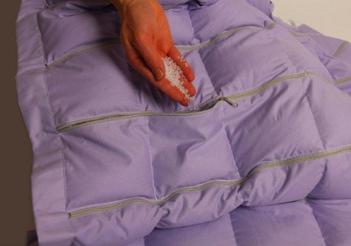 Кармашки одеяла, один из них расстёгнут, в нём виден синтетический наполнитель в виде бесцветных шариков