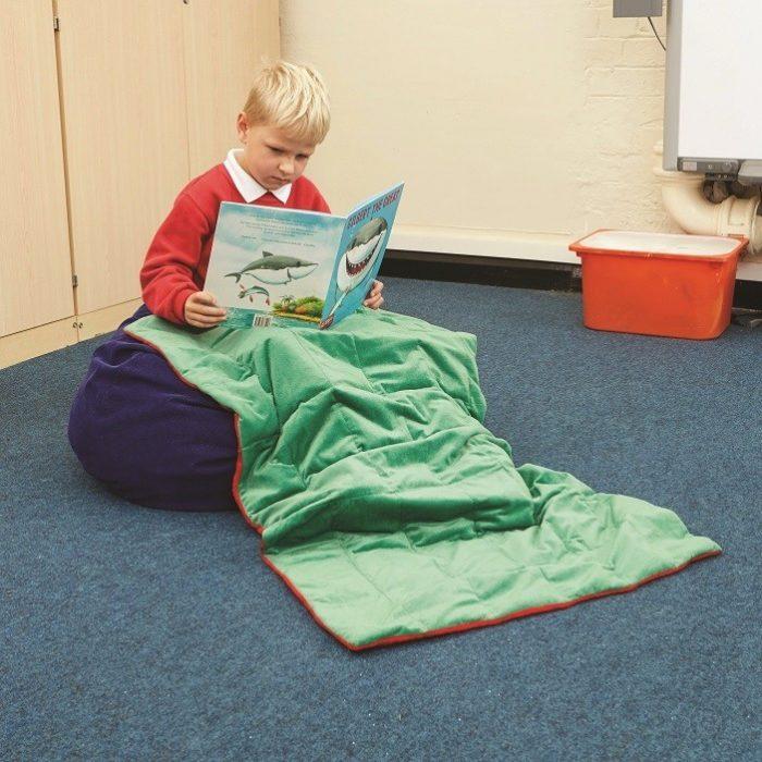 Мальчик читает книгу, его ножки прикрыты тяжёлым одеялом