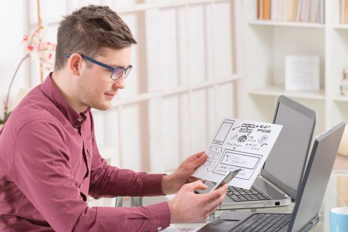 Мужчина с бумажным макетом и телефоном в руках
