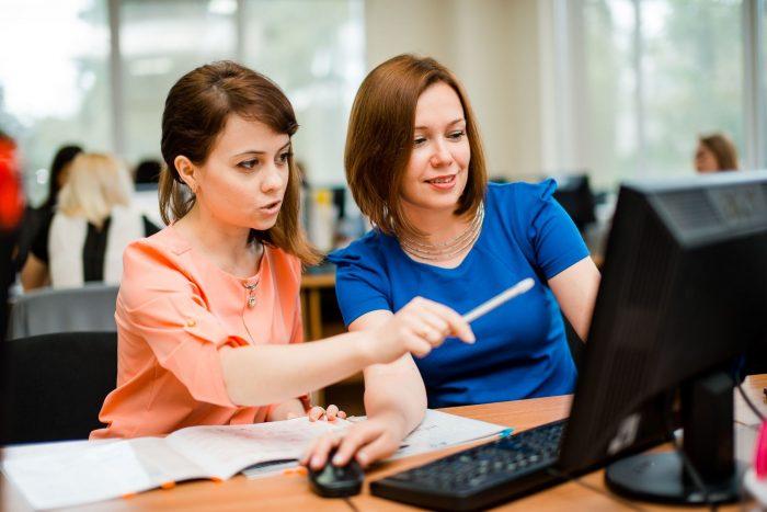 Две девушки обсуждают изображение на мониторе