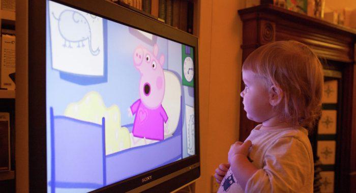Маленькая девочка (примерно 1–1,5 года) смотрит мультфильм «Свинка Пеппа» по телевизору