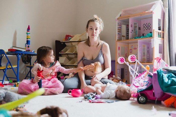 Уставшая мама с двумя детьми сидит на полу с потерянным видом