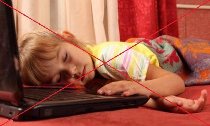 Девочка спит возле оnкрытого ноутбука