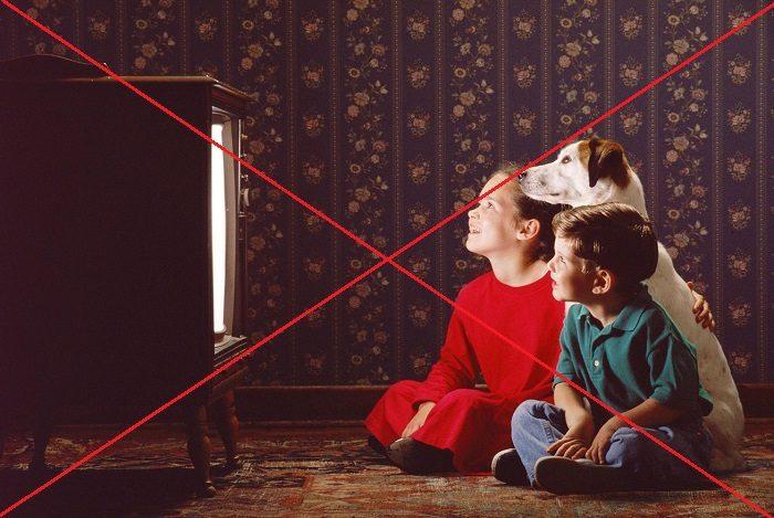 Дети сидят близко к телевизору и смотрят на экран, с ними сидит собака
