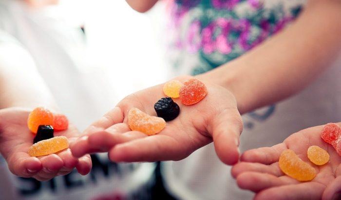 Сухофрукты и конфеты на ладонях у детей