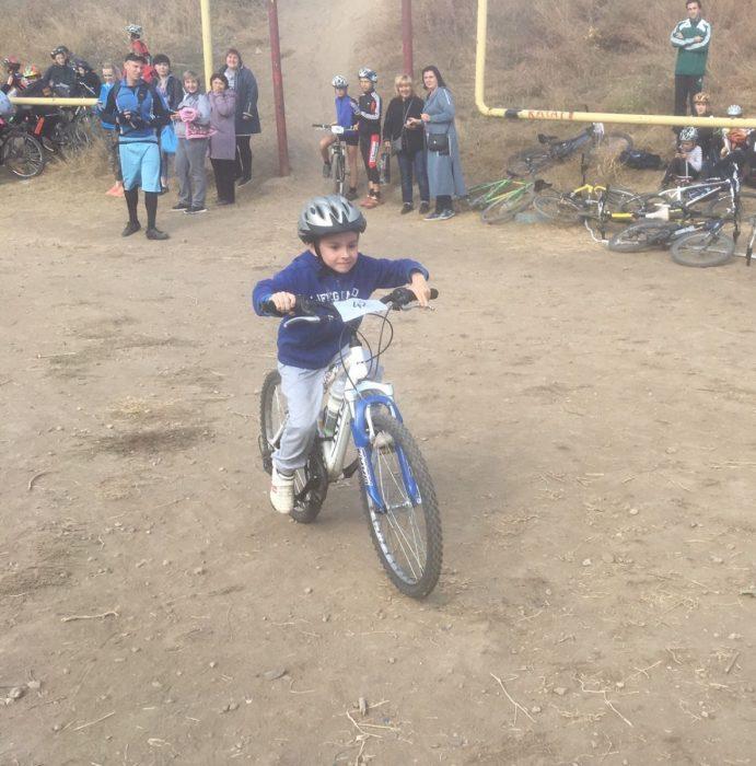 Малыш едет на велосипеде с алюминиевой рамой и большими колёсами