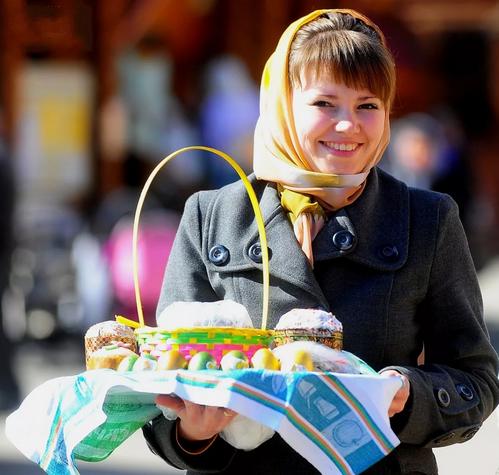 Улыбающаяся девушка держит поднос с куличом и яйцами