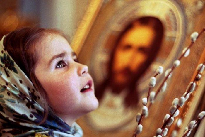 Девочка в храме с удивлением смотрит вверх, держа веточку вербы