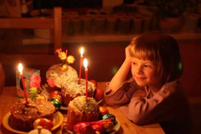 Девочка сидит за столом и любуется на пасхальные куличи