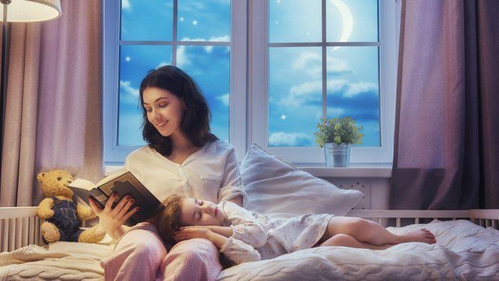Мама читает засыпающей девочке на ночь книжку