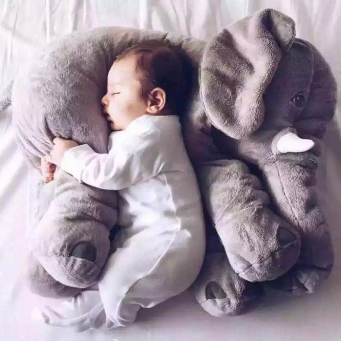 Маленький ребёнок спит с большим игрушечным слоном