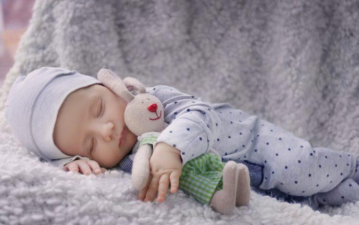 Малыш спит с игрушечным зайцем из мягкой ткани
