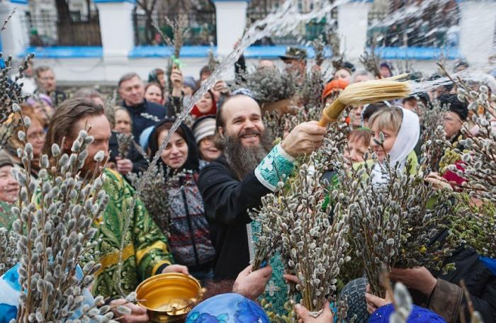 Православный батюшка освящает вербу
