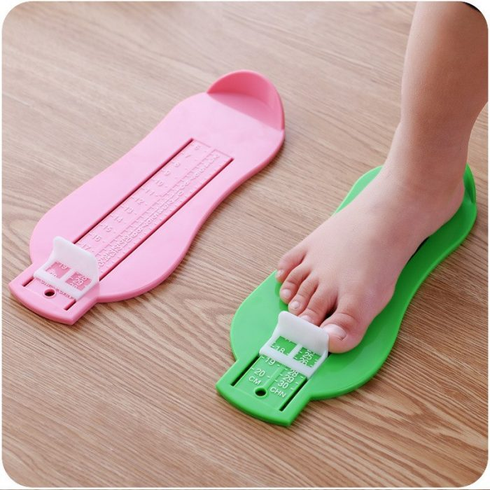 Нога ребёнка стоит на приспособлении для измерения длины стопы