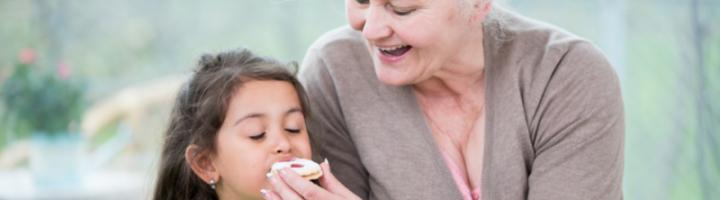 бабушка кормит внучку пирожными