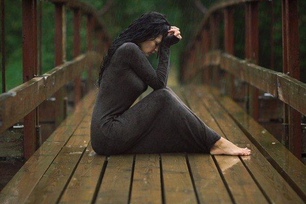 Расстроенная женщина сидит на мосту и держится за голову