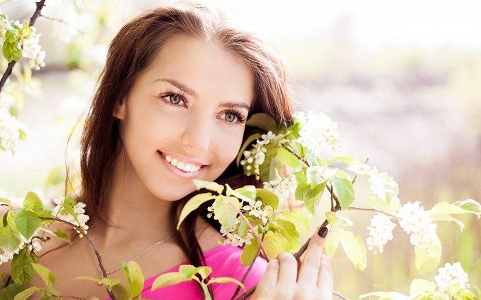 Девушка мило улыбается, держа в руках цветущую ветку дерева