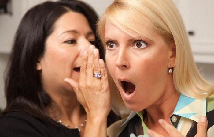 Одна женщина что-то шепчет на ухо другой, та открывает рот от удивления