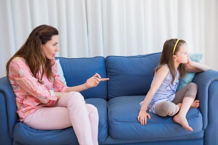 Мама ругает дочку, грозит ей пальцем; девочка отвернулась с недовольным видом