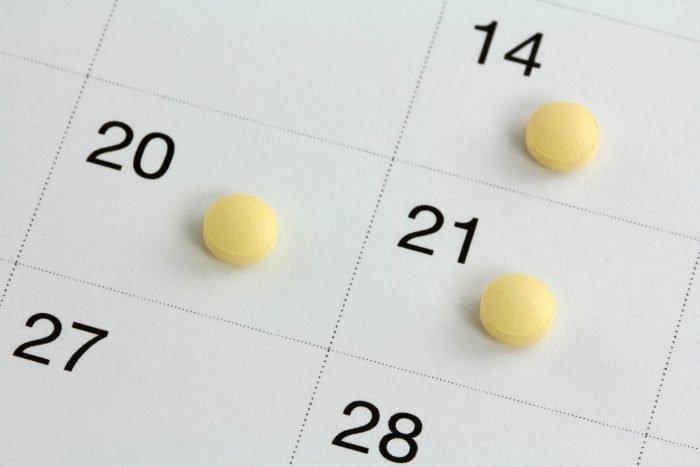 Три таблетки лежат на датах в календаре