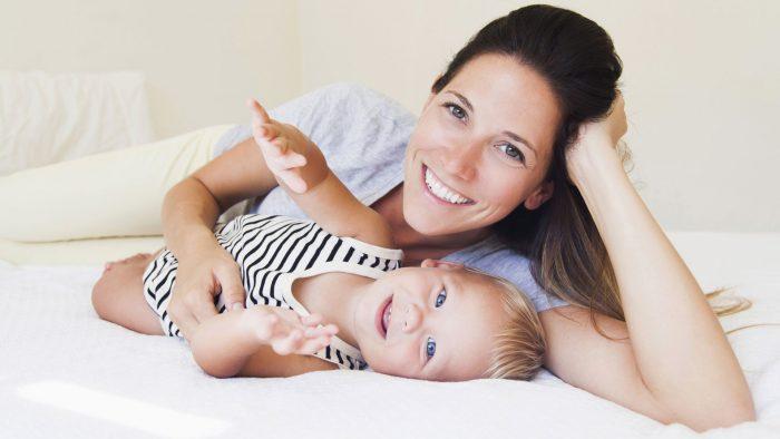 Девушка лежит на кровати с малышом