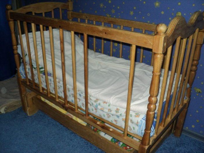 С боковой стенки кроватки снять две рейки