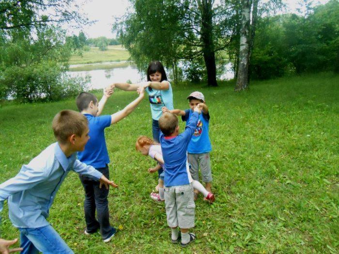 Пятеро детей и молодая женщина играют на природе