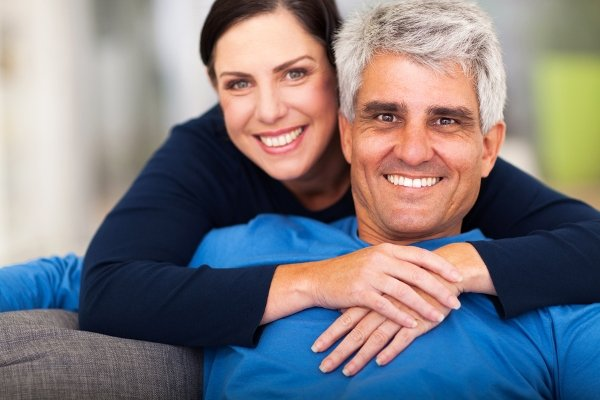 Женщина обнимает пожилого мужчину, они счастливо улыбаются