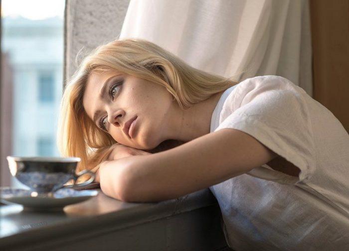Девушка грустит, сидя у окна с чашкой